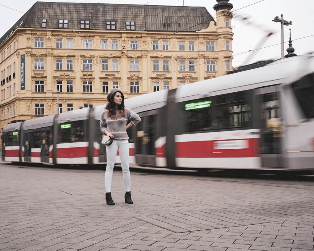 žena stojaca pred iducou električkou oblečená v sivom pulovri, bielych rifliach a čiernych členkových čižmách so striebornou mini kabelkou na pleci a baretkou na hlave