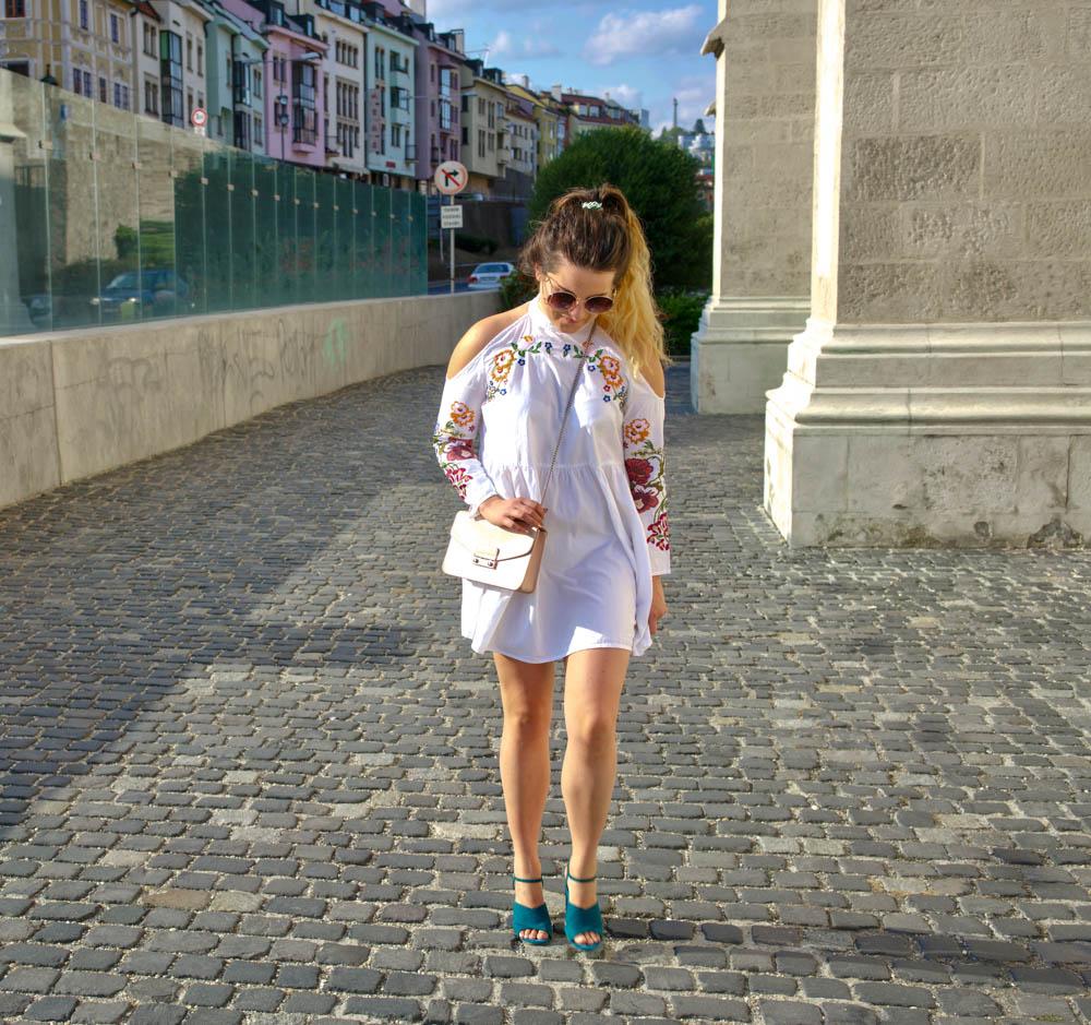 žena pozerajuca sa do zeme v bielych vyšívaných šatách, slnečných okuliaroch, ružovej kabelke a zelených sandáloch