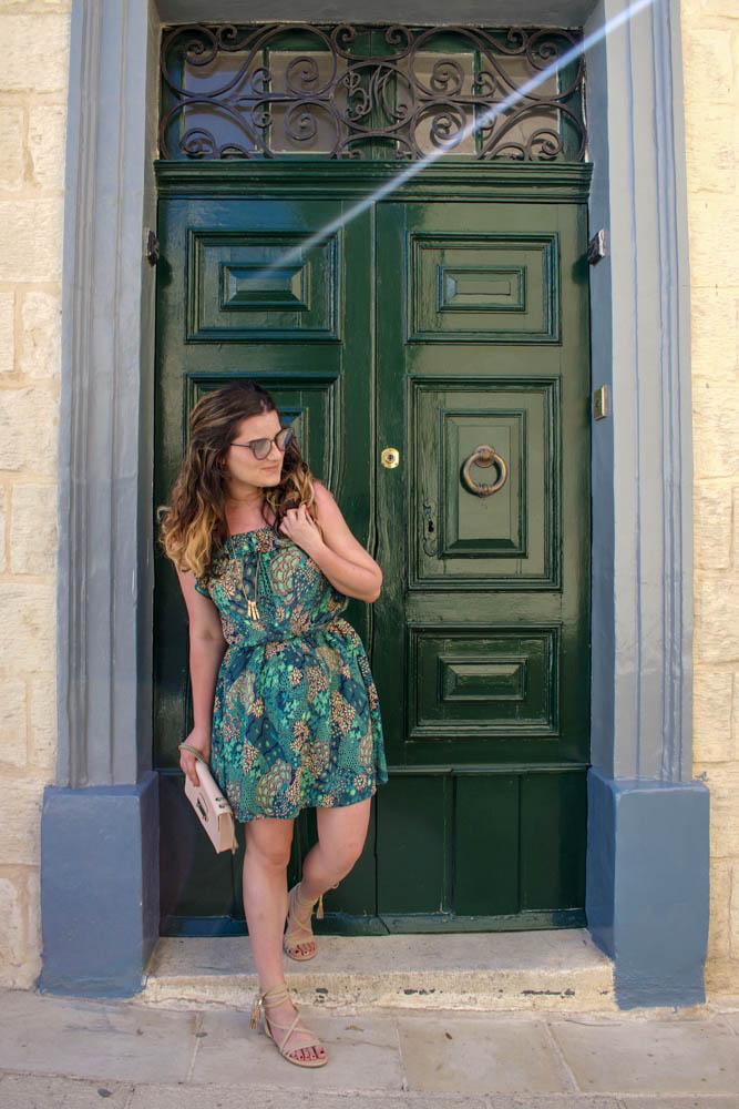 žena stojaca pred zelenými dverami v krátkych letných šatách s bledoružovou kablekou v ruke