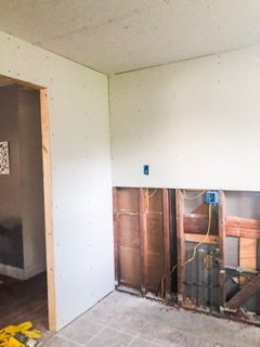 finishing up the load bearing wall is as plain as drywall, and the edges were mudded instead of framed with wood.