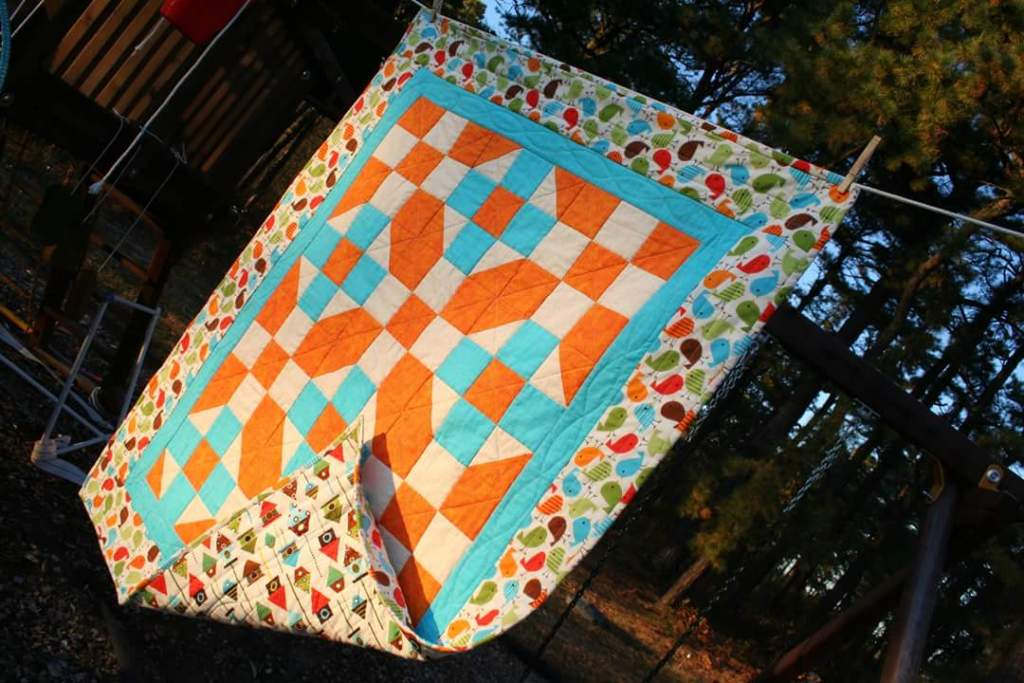 Bird themed quilt in orange and blue