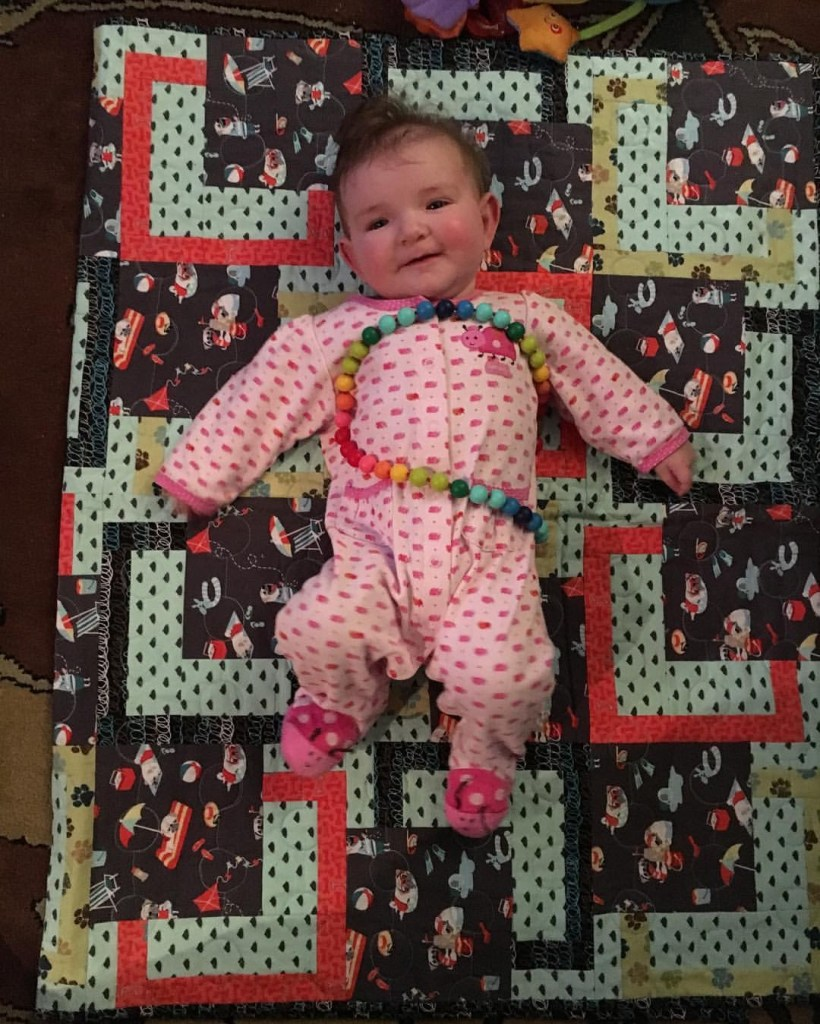 baby on a quilt covered in pugs and poo
