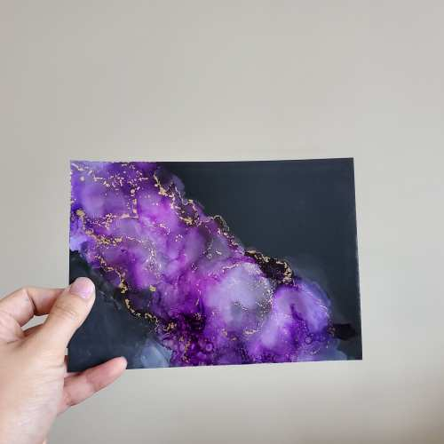 hand holding a piece of alcohol ink art called Electric Violet