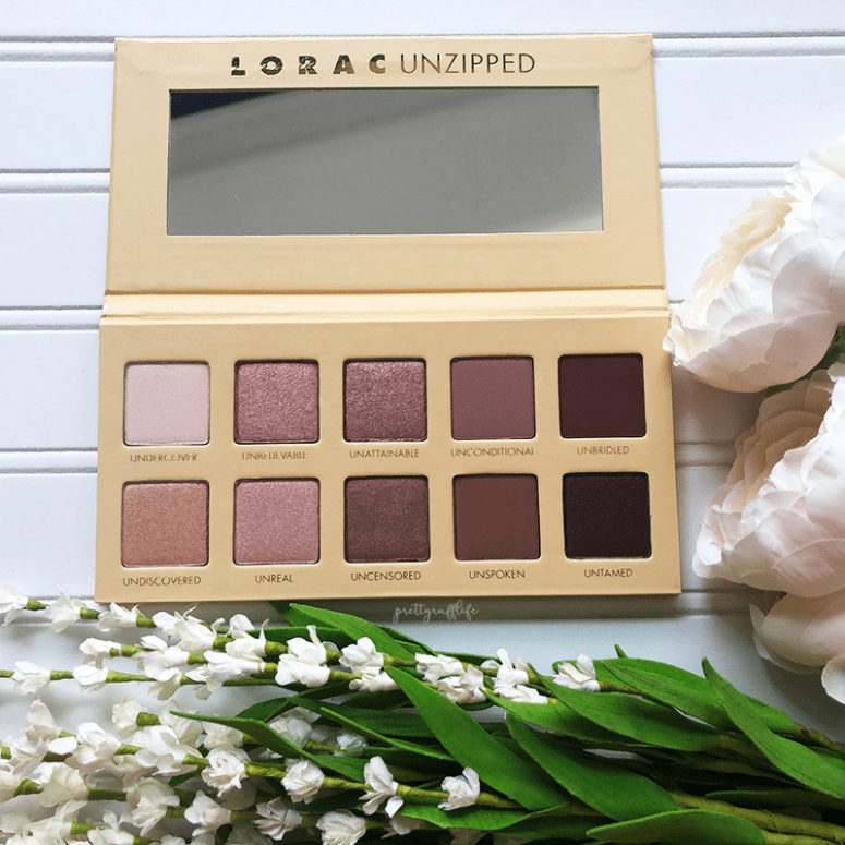 open lorac unzipped palette on a white background with white flowers