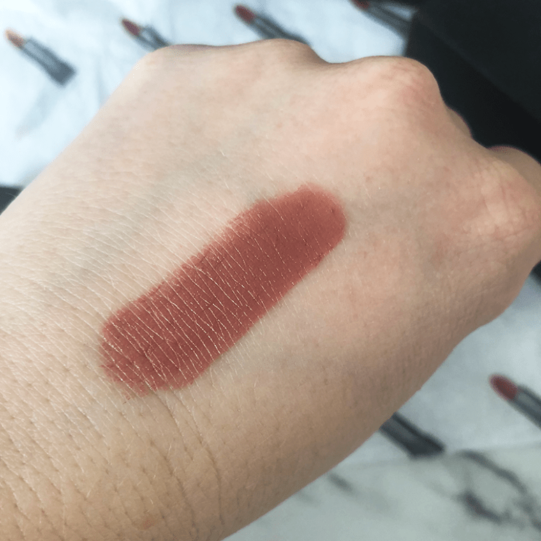 A hand swatch of a nude beige Bite Beauty lipstick