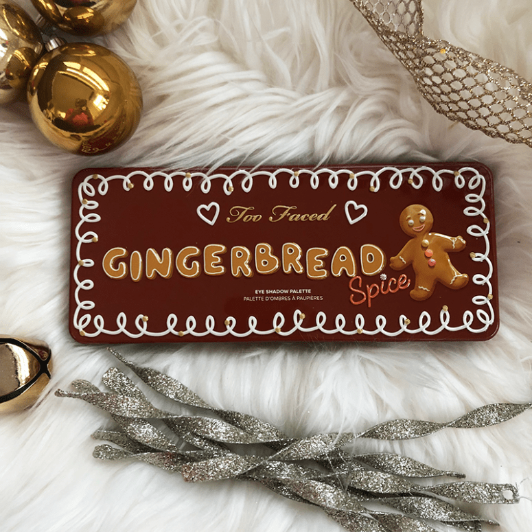 The Too Faced Gingerbread Spice Eyeshadow palette on a white fuzzy background with gold Christmas decorations surrounding it
