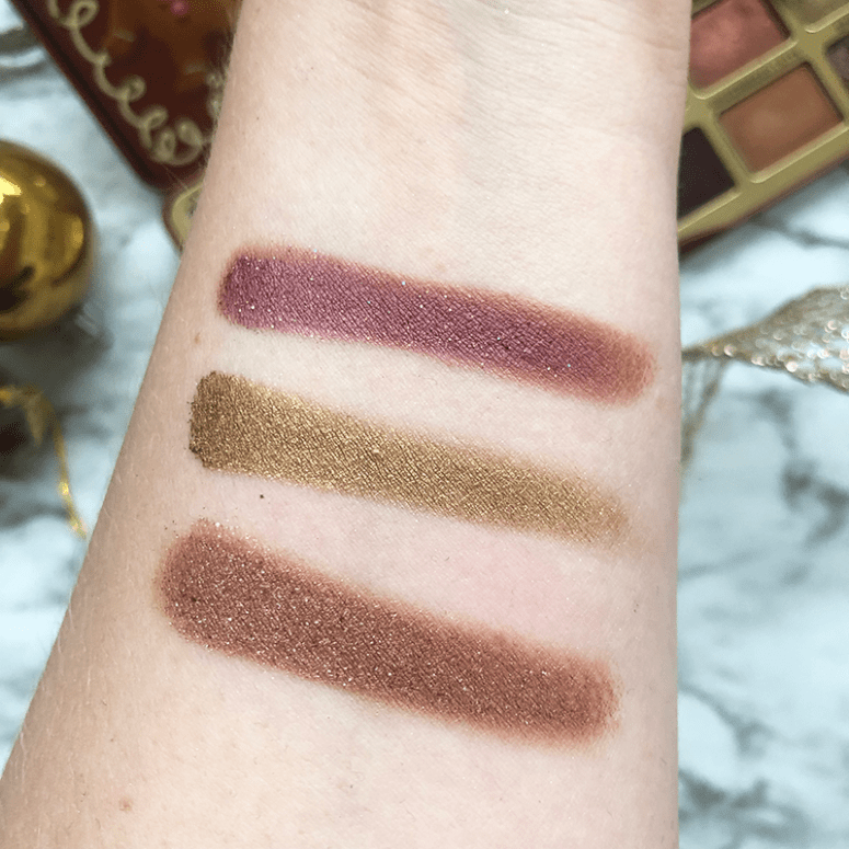 Swatches of three shadows from the Too Faced Gingerbread Spice Eyeshadow palette: Ooo Burn! (Metallic Sparkly Plum) ; Spice of Life (Metallic Olive Green); Spiced Rum (Metallic Medium Brown)