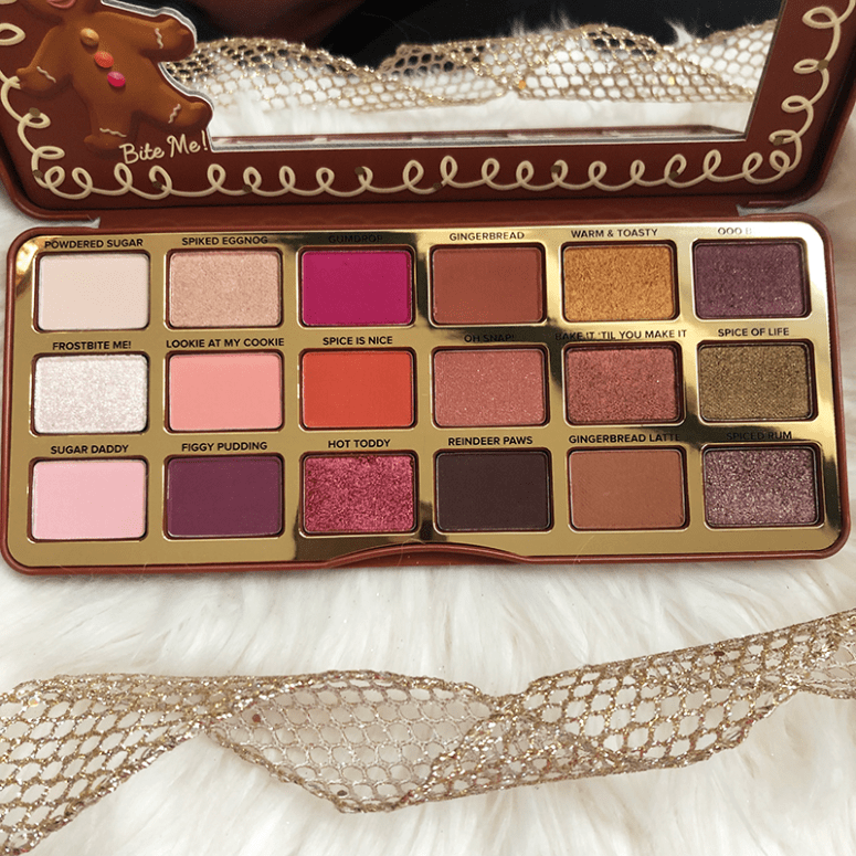 Too Faced's Gingerbread Spice Eyeshadow palette open on a white fuzzy blanket and a gold ribbon below it