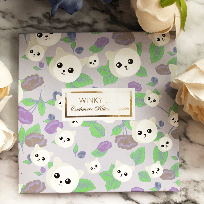 a picture of the Winky Lux Cashmere Kitten Palette on a marble background with white flowers in the background