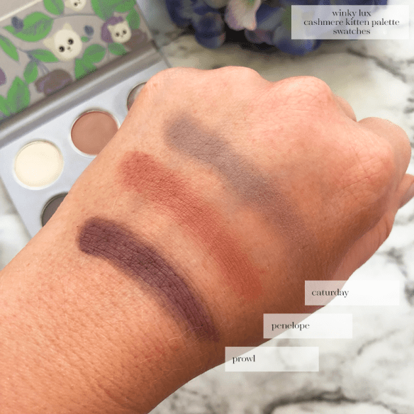 hand swatches of the Winky Lux Cashmere Kitten Palette in the shades Caturday (matte grey plum); Penelope (Satin dusty rose); Prowl (Satin smokey plum)