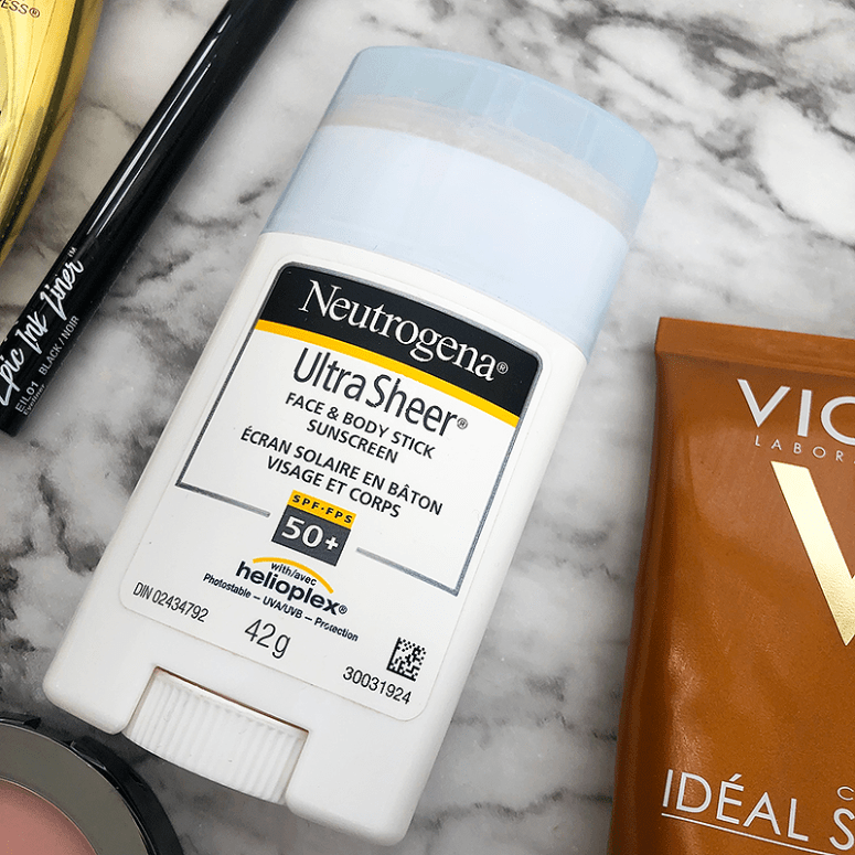 a close up shot of Neutrogena's UltraSheer Face + Body Stick Sunscreen laying on a marble background