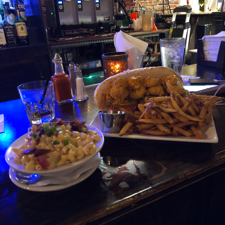 A picture of the shrimp po'boy and mac n cheese sitting on a bar from Saint Lawrence Gastropub in New Orleans
