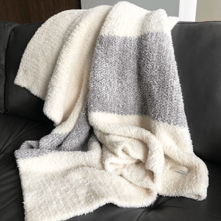 a white and gray throw placed casually on a dark gray couch