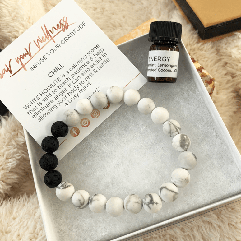 a white and black aromatherapy bracelet sitting in a white box with a description card and small vial of essential oil
