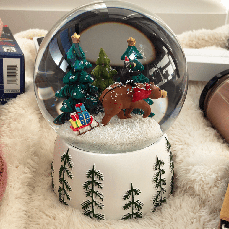 a picture of a snowglobe with a bear pulling a sled with gifts on it