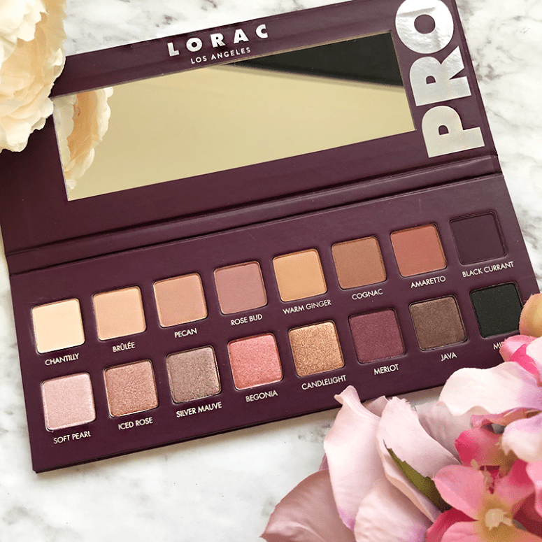 a picture of an open Lorac Pro 4 eyeshadow palette on a marble background with flowers around it
