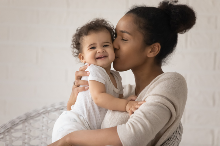 Close up loving young African American mother kissing toddler daughter stock photo