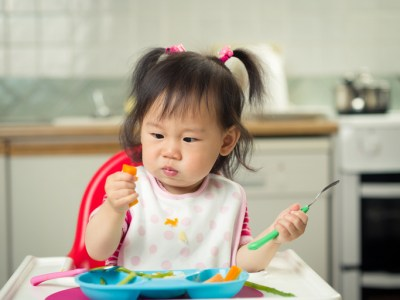 baby girl eating carrot at home