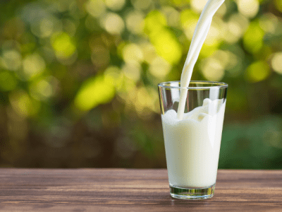 .org Pouring milk in the glass on the background of nature