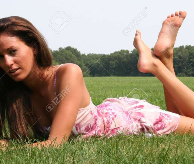 Barefoot Girl Relaxing In The Grass Stock Photo