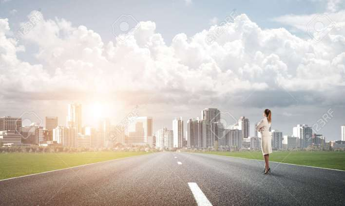 elegant businesswoman on road standing with back and looking ahead stock photo, picture and royalty free image. image 64822643.