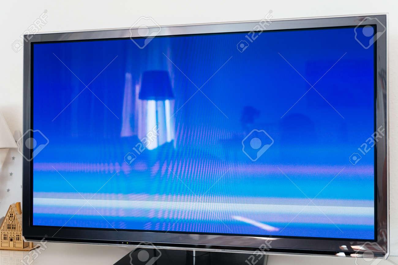 grand ecran tv plasma 4k moderne dans le salon avec aucun ecran bleu siganl reflet du salon a l interieur