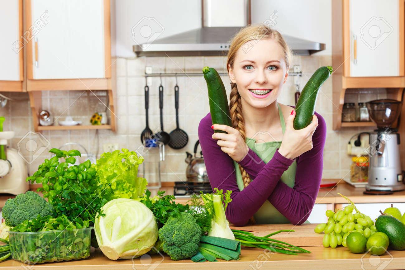 femme dans la cuisine avec beaucoup de legumes verts a feuilles produits frais organiquement sur le comptoir jeune femme au foyer heureux holding
