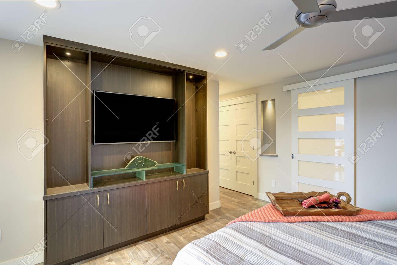 un interieur contemporain avec une chambre et un vetement recouvert d une couverture rouge jette un regard sur un meuble de television integre
