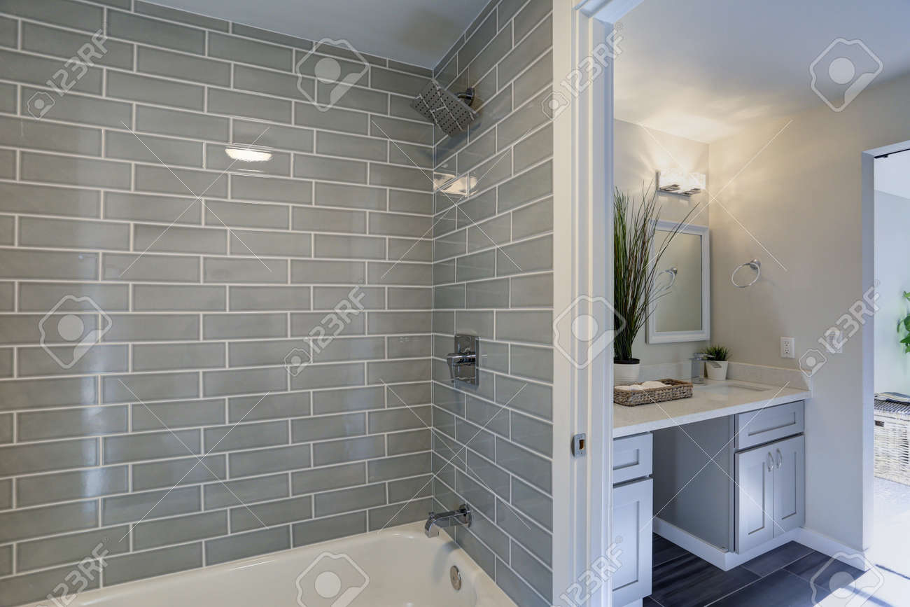 warm and clean bathroom boasts grey glass tile shower surround