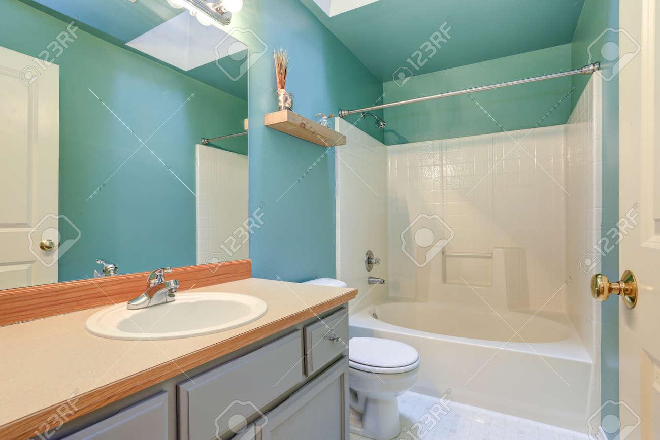 interieur de salle de bain bleu vert vif avec vanite de salle de bain gris clair et combinaison de baignoire et douche blanche eclairee par un puits