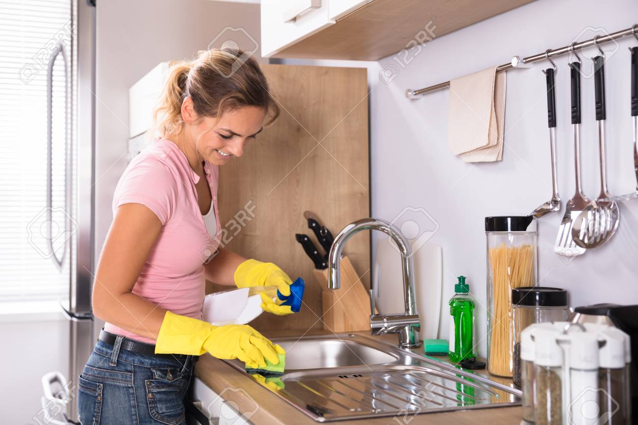 happy young woman cleaning kitchen sink with sponge and spray stock photo picture and royalty free image image 92388804
