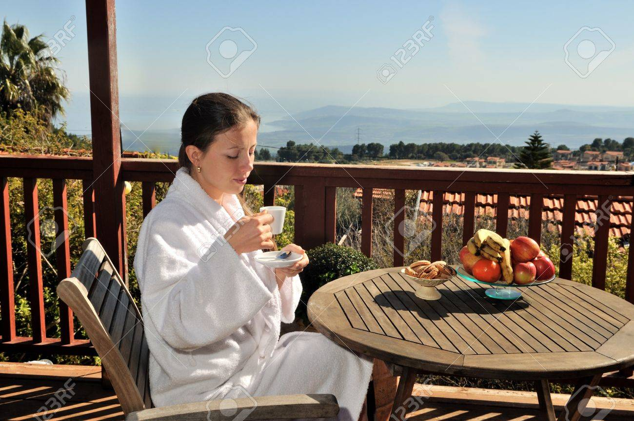 young girl sits at a table on the porch and drink coffee