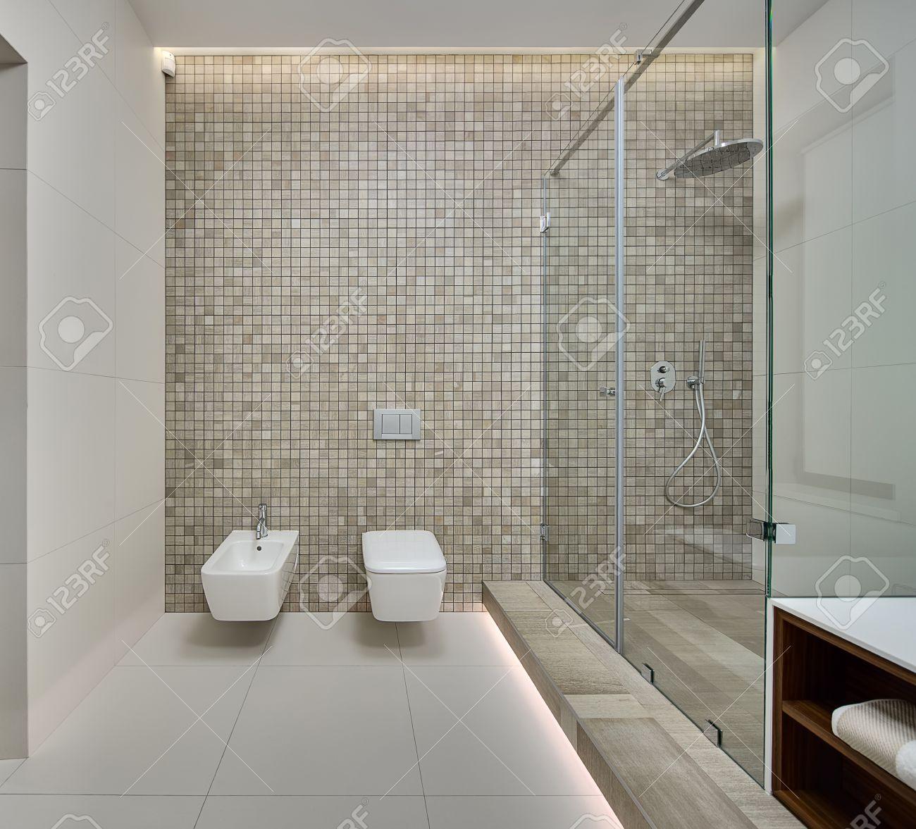 salle d eau dans un style moderne paroi arriere decoree de mosaique beige sur le mur arriere il y a un bidet blanc toilette et commutateurs blanc sur la droite il y a