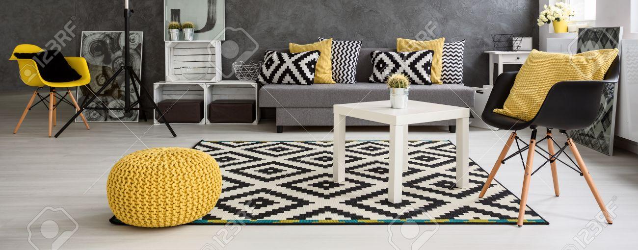 panorama d un spacieux salon moderne agencee dans le style scandinave meuble en gris et blanc avec des elements jaunes