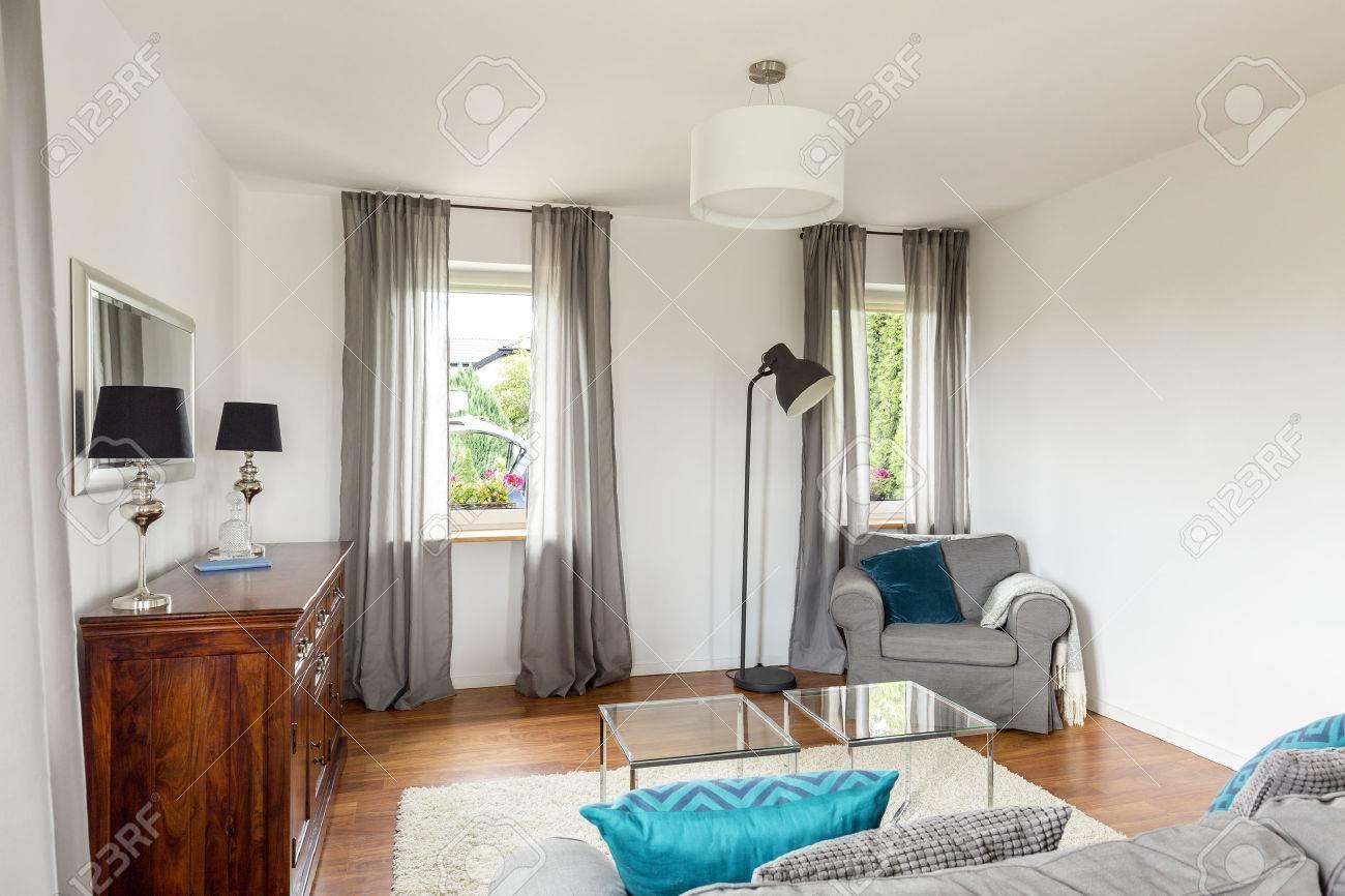 petit salon avec buffet elegant table en verre un canape et fenetre rideaux decoratifs