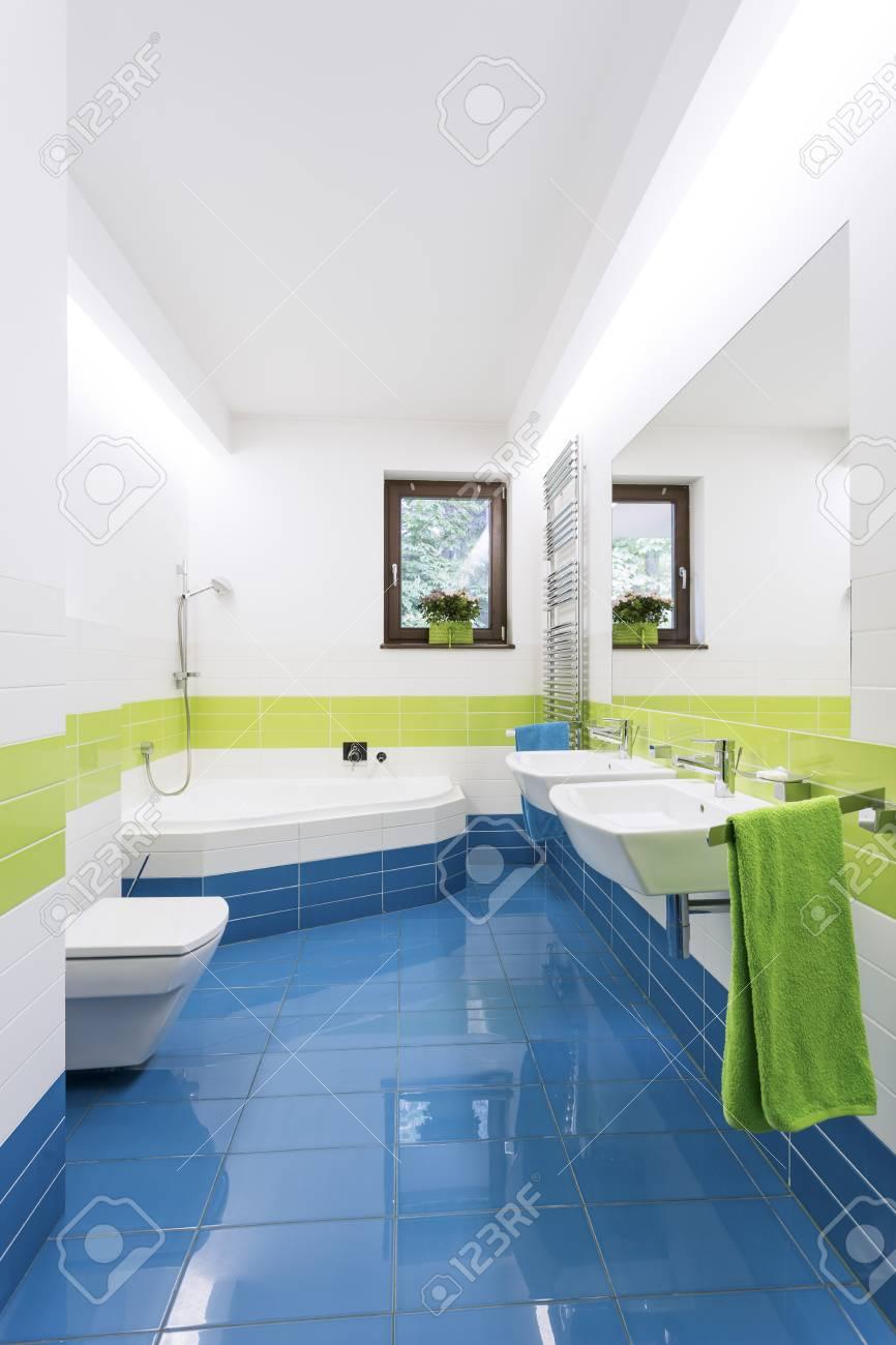 salle de bain moderne coloree avec baignoire lavabos et toilettes avec carrelage bleu et vert