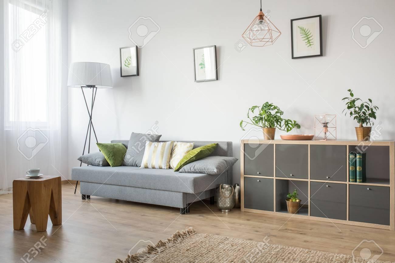 chambre avec table d appoint en bois tapis bibliotheque et canape gris