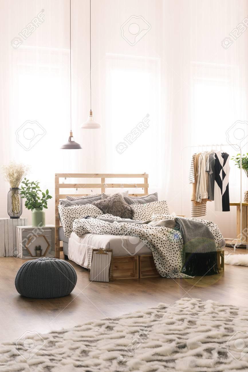 spacieuse chambre lumineuse avec tapis lit vetements et pouf banque d images et photos libres de droits image 78104247
