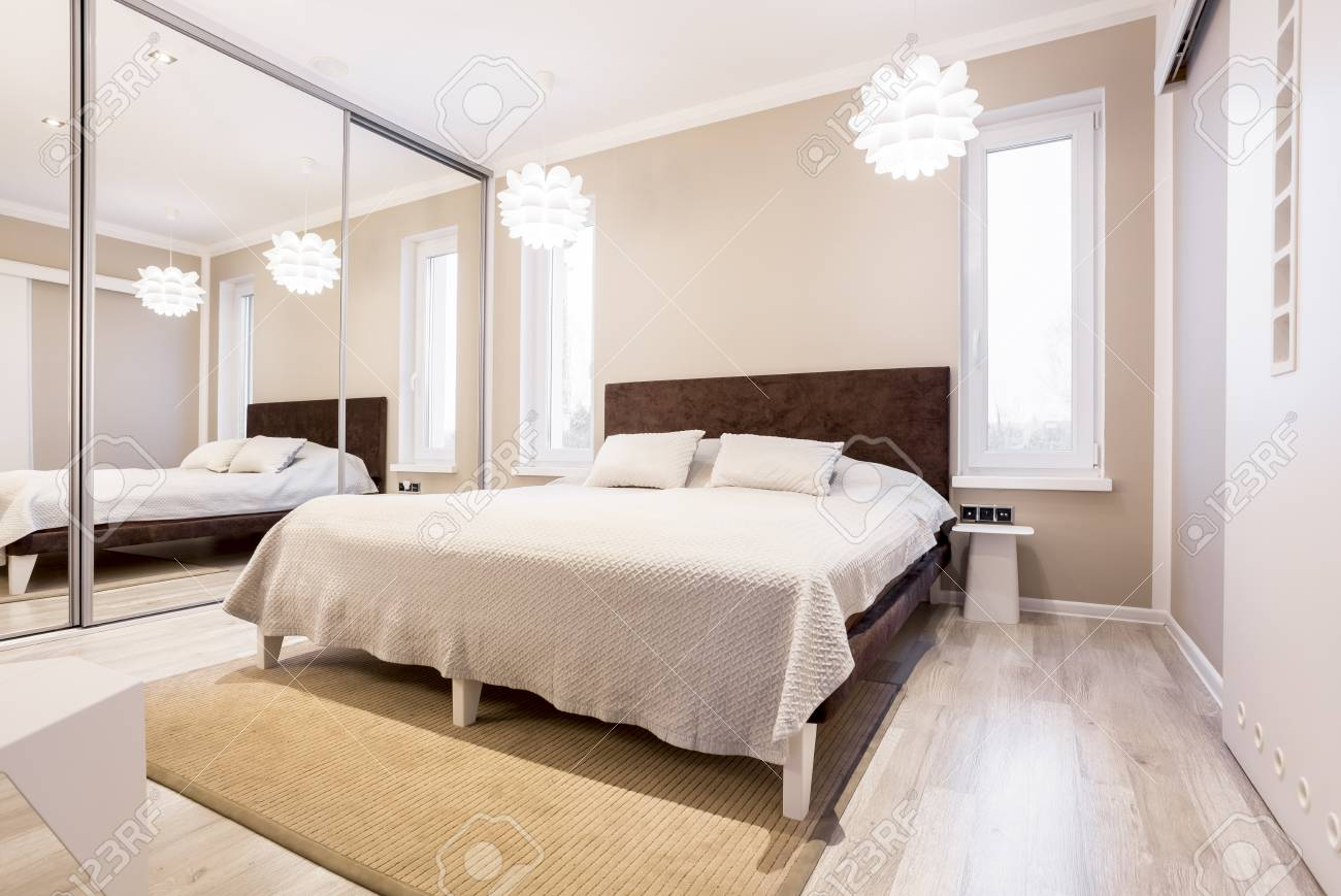 toned beige bedroom with mirror wardrobe and simple bed stock photo picture and royalty free image image 84520275