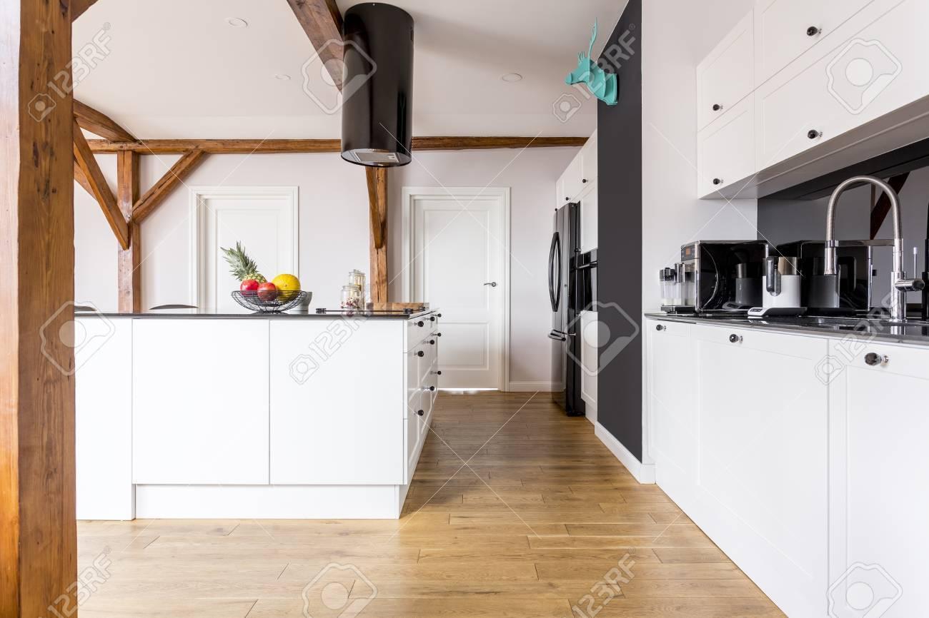 spacieuse cuisine noir et blanc avec des fruits dans un bol sur le comptoir de l ilot de cuisine et un decor bleu sur le mur noir banque d images et photos libres de