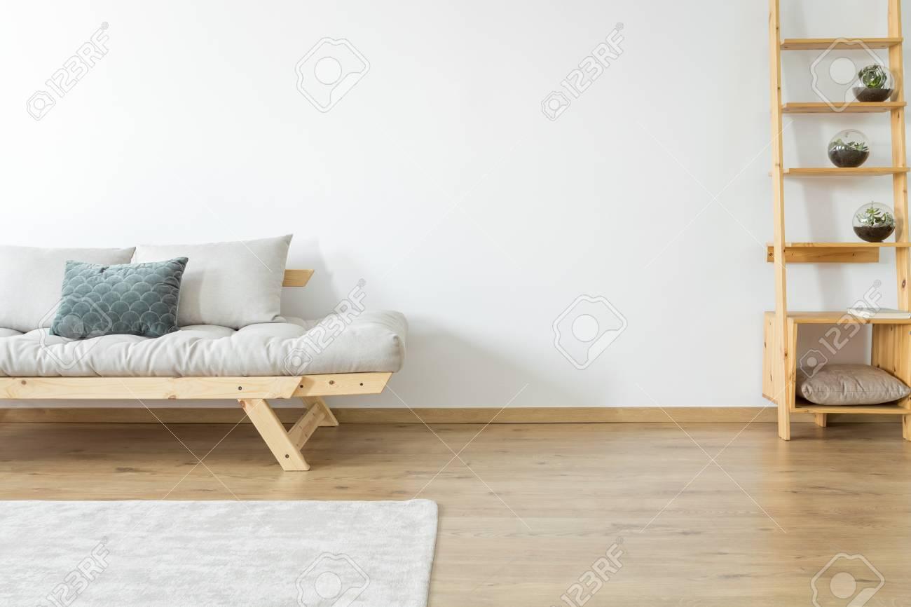 espace de copie de mur blanc et de tapis sur le sol dans le salon beige avec decoration sur des etageres en bois pres d un canape avec des oreillers banque d images et