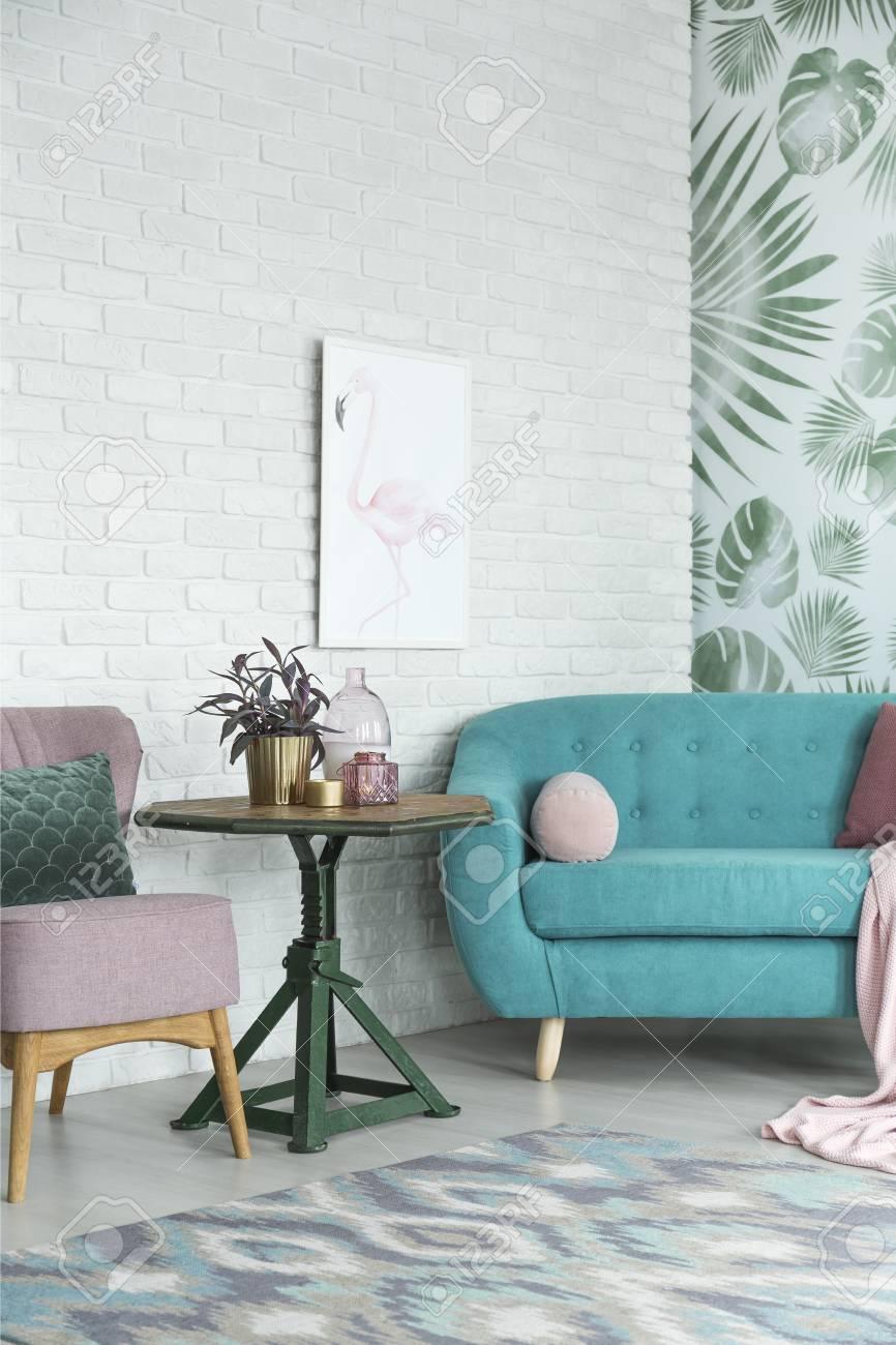 banque d images table verte avec plante entre canape turquoise et chaise rose contre le mur de briques blanches avec affiche dans le salon