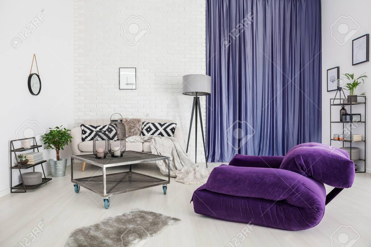 fauteuil violet et tapis gris dans un salon interieur moderne avec une table en metal devant un canape avec un canape de carreaux a cote de tissu et de tissu de satin