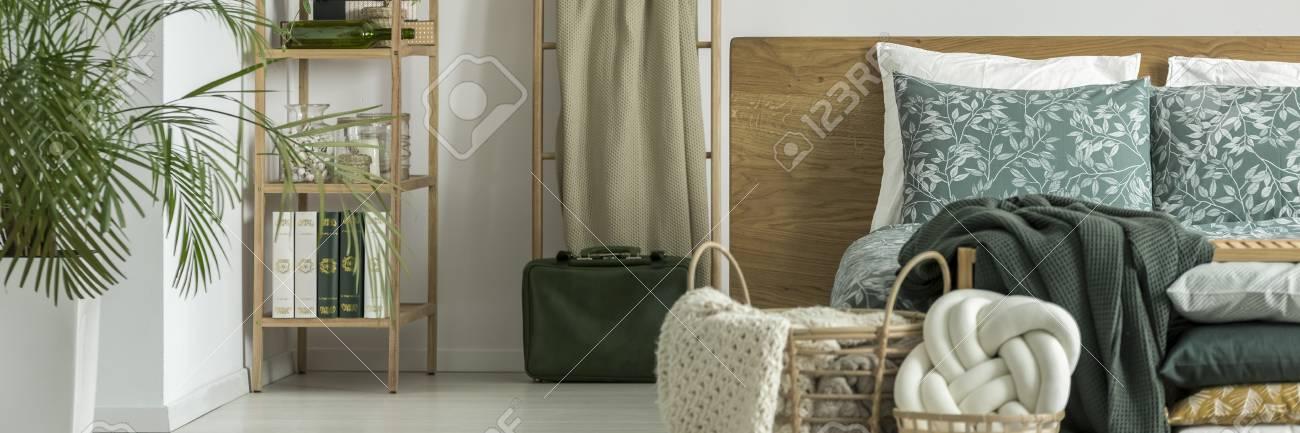 https fr 123rf com photo 93434455 valise en cuir vert debout c3 a0 c c3 b4t c3 a9 de lit avec le couvre lit en bois et des coussins floraux dans l amp 39 html