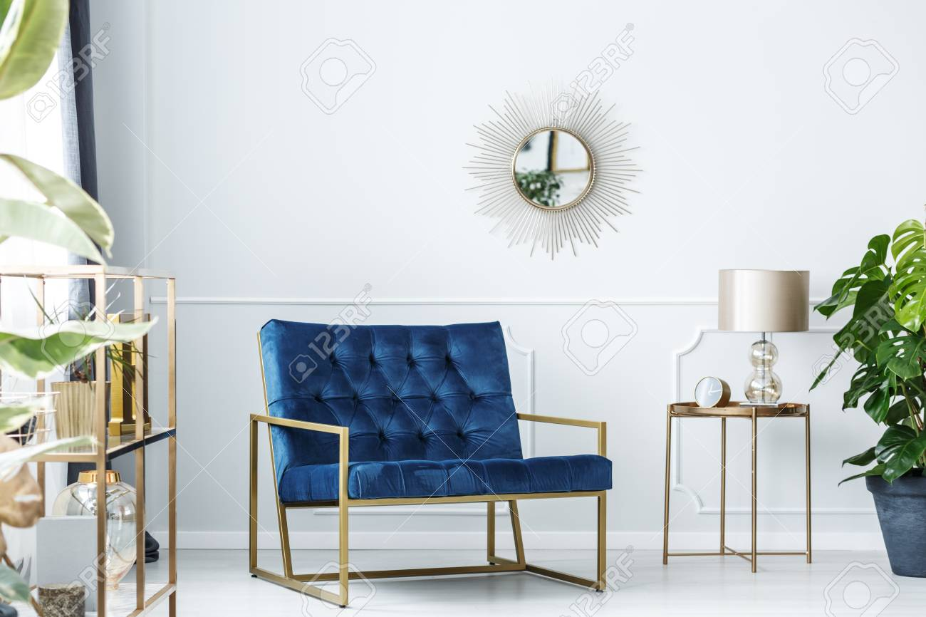 navy blue armchair next to gold table with lamp against white stock photo picture and royalty free image image 97864848