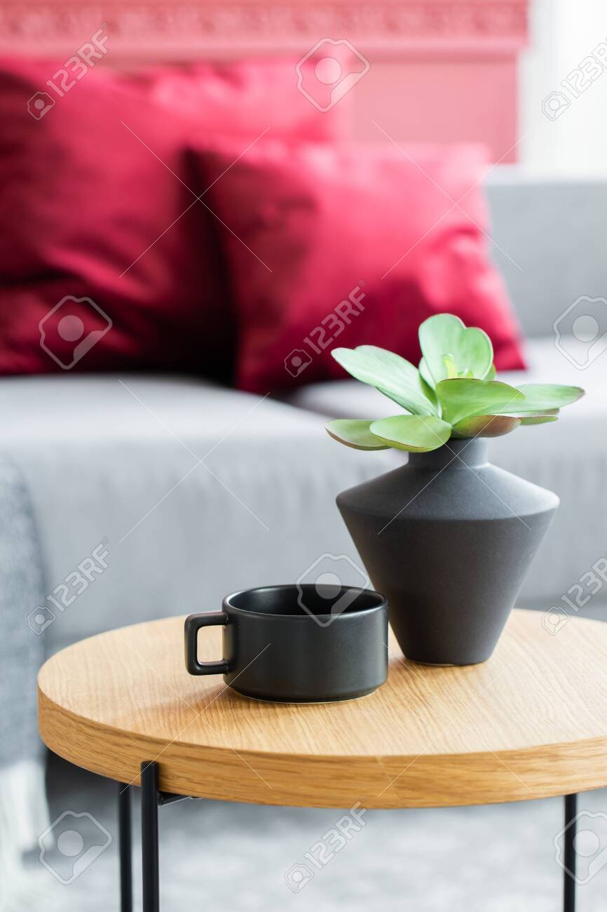 https www 123rf com photo 141007828 green flowers in black vase next to black coffee cup on wooden coffee table in stylish interior html