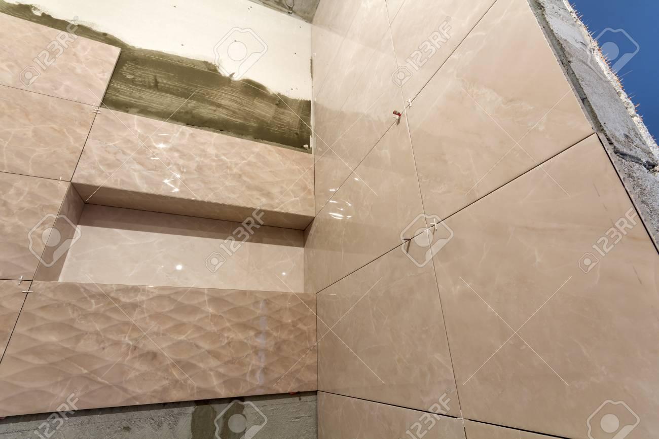 unfinished work light beige ceramic tiles installed on walls