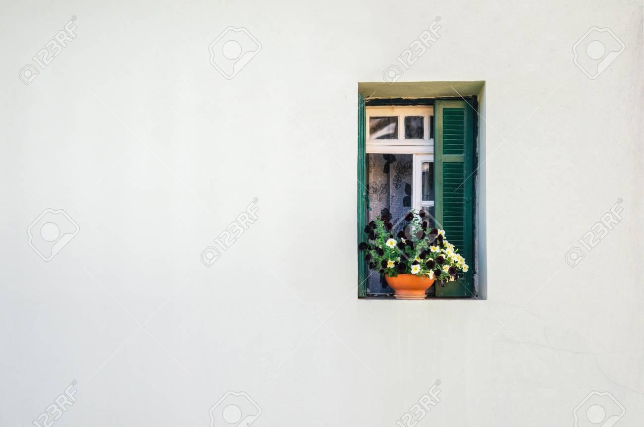 vue de la maison en pierre blanche et de la petite fenetre verte avec les rideaux et le petit pot de fleurs colorees minimalisme et espace libre pour le concept de fond