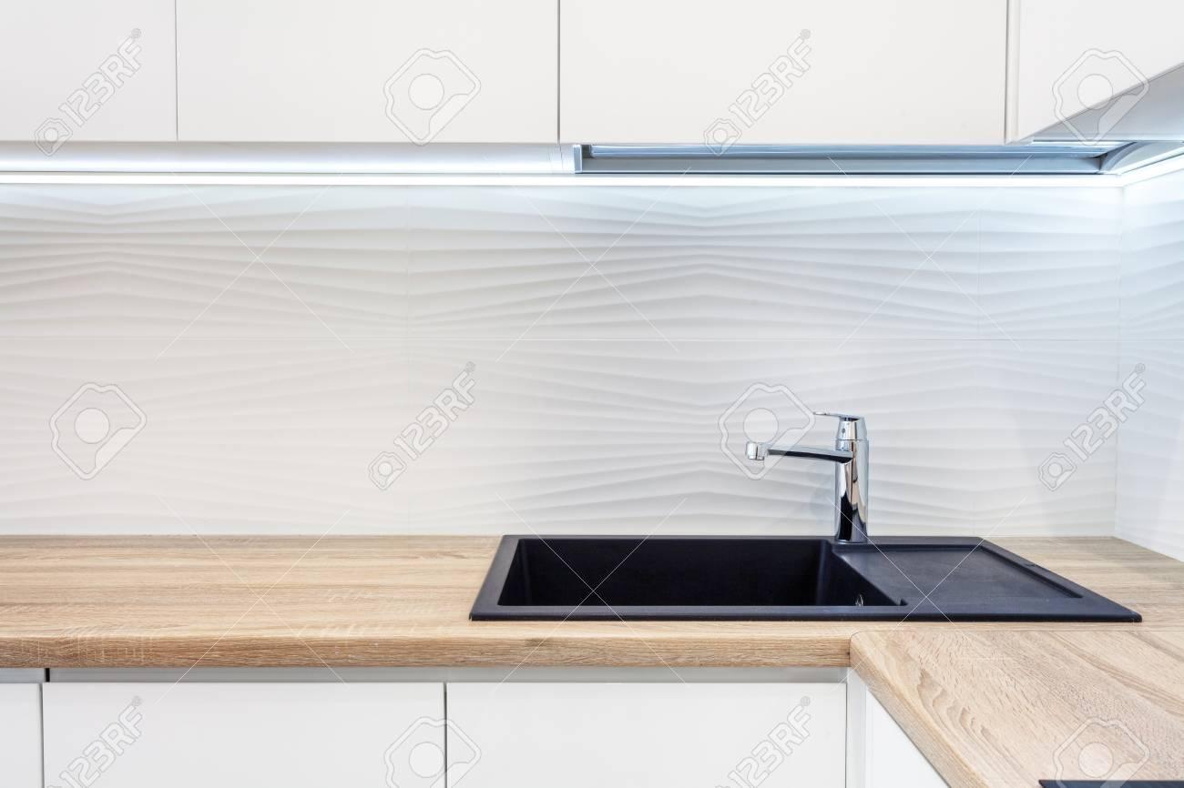 modern designer chrome water tap over black new kitchen sink