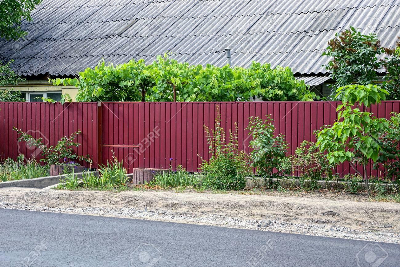 partie de la cloture de fer rouge et la porte devant la maison
